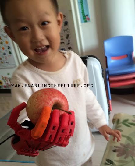 Bambino cinese con una mela nella mano artificiale