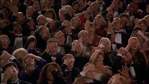"""Un gruppo di persone, ciascuna si sta dando una manata sulla fronte. Dal film """"Pallottola spuntata 33 1/3""""."""