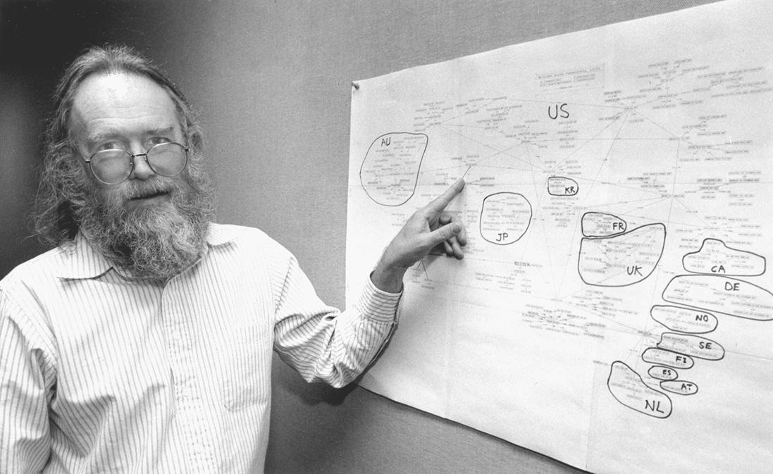 Jon Postel mostra una mappa dei nomi di dominio Internet disegnata a mano e appesa a un muro. Foto da Wikimedia